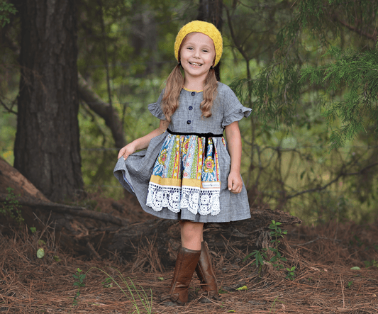 DARLING AND UNIQUE ARE THE PERFECT WORDS TO DESCRIBE YOUR LITTLE GIRL ... AND THIS EYE-CATCHING DESIGN! A DARK GRAY CHAMBRAY DRESS WITH PLEATED SLEEVES IS TOPPED BY A COLORFUL APRON WITH A SWEET, LACE HEM.  LITTLE TOUCHES, LIKE A ROW OF BUTTONS ENDING AT A RIBBON BOW AND A FLASH OF COLOR PEEKING FROM THE POCKETS, WILL HAVE HER SMILING WITH DELIGHT.
